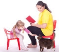 Little girl and mother with book and cat Stock Photo