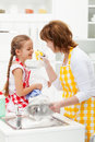 Little girl and mother having fun washing the dishes with foam together Royalty Free Stock Photo