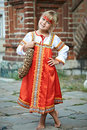 Little girl in national costumes in russian village on summer day Stock Photos