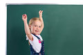 Little girl near blackboard with chalk in hand up standing on white background Stock Images