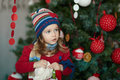 Little girl near the christmas tree in a celebratory dress Stock Images