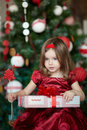 Little girl near the christmas tree in a celebratory dress Royalty Free Stock Images