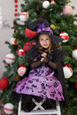 Little girl near the christmas tree in a celebratory dress Stock Image