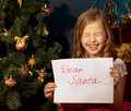 Little girl near Christmas tree  writing letter for Santa Stock Image