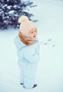 Little girl near the fir tree standing in snowy weather Stock Images
