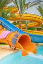 Little girl near water park slides beautiful stands large orange Royalty Free Stock Image