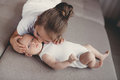 Little girl with a newborn baby brother five years old brunette dressed in white shirt and white pants spends time together her Royalty Free Stock Photo