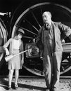 Little girl with an oil can standing next to a locomotive and the engine driver Royalty Free Stock Photo