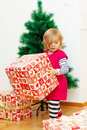 Little girl opens the gift holding a christmas at home with tree in background Royalty Free Stock Photo