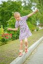 Little girl oscillates on curb beautiful pavement Royalty Free Stock Photos