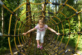 Little girl in outdoor park attractions going trought tunnel forest attraction Royalty Free Stock Images