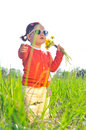 Little girl outdoors with flowers in sunglasses on meadow Stock Photos