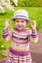 Little girl outdoors wearing hat beautiful blond in beautiful with cars Royalty Free Stock Image