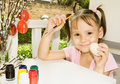 Little girl painting easter eggs sitting on terrace and Royalty Free Stock Image