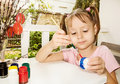 Little girl painting easter eggs sitting on terrace and Stock Photography