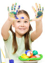 Little girl is painting eggs preparing for easter showing her hands over white Stock Photo