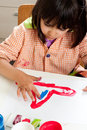 Little girl painting with fingers concentrated Stock Photos
