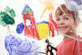 Little girl paints on glass and smiles