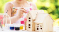 Little girl paints wooden model of house Royalty Free Stock Photo
