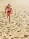 Smiling little blonde girl in dress runs at summer day