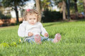 A little girl in the park is sitting on grass Royalty Free Stock Photography