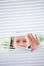 Little girl peeking through blinds from outside Royalty Free Stock Photos