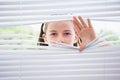 Little girl peeking through blinds from outside Stock Image
