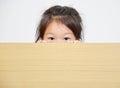little girl peeking over table.