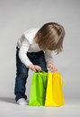 Little girl peeping into a shopping bag grey background Stock Photos