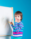 Little girl with pencil at easel Royalty Free Stock Photos