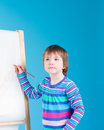 Little girl with pencil at easel Royalty Free Stock Photo