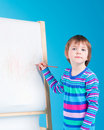 Little girl with pencil at easel Royalty Free Stock Image