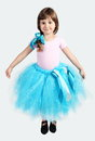 Little girl performing in tutu skirt studio shot over grey Royalty Free Stock Image
