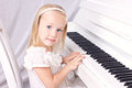 Little girl at piano beauy blond in white beautiful dress sitting white looking camera Royalty Free Stock Photos