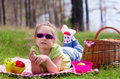 Little girl with picnic basket and grape at lawn Royalty Free Stock Image