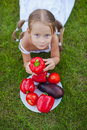 Little girl with pigtails in a garden with a plate of vegetables this image has attached release Stock Photos