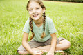 little girl with pigtails sitting cross legged on the grass