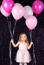 Little girl with pink balloons and white is studio Stock Image