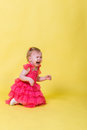 Little girl in pink dress kneeling and crying on a yellow background