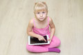 Little girl in a pink dress looking up and presses on the tablet