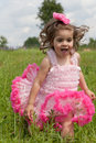 Little girl in a pink dress runs on grass Stock Images