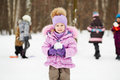 Little girl in pink jacket with fur collar stands in winter park holding snowball several children play behind her not focus Stock Image