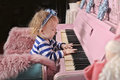 Little girl with a pink piano Stock Photo