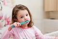 Little girl in pink pyjamas in bathroom brushing teeth Royalty Free Stock Photo