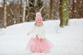 Little girl in a pink skirt in winter smiles in the park Royalty Free Stock Photo