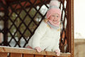 A little girl in a pink skirt in winter smiles in a park in a ga Royalty Free Stock Photo