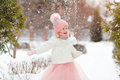 Little girl in a pink skirt in winter smiles in the park and thr Royalty Free Stock Photo