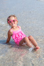 Little girl in pink swimsuit and sunglasses sitting in the sea posing at camera. Happy, smiling. Summer vacation. Royalty Free Stock Photo