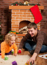 Little girl play with dad  near Christmas tree Stock Image