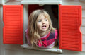 Little girl in playground blond looking through the window of kids playhouse Royalty Free Stock Images